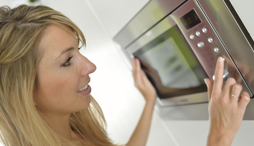 bigstock-Woman-at-home-using-microwave-56373941