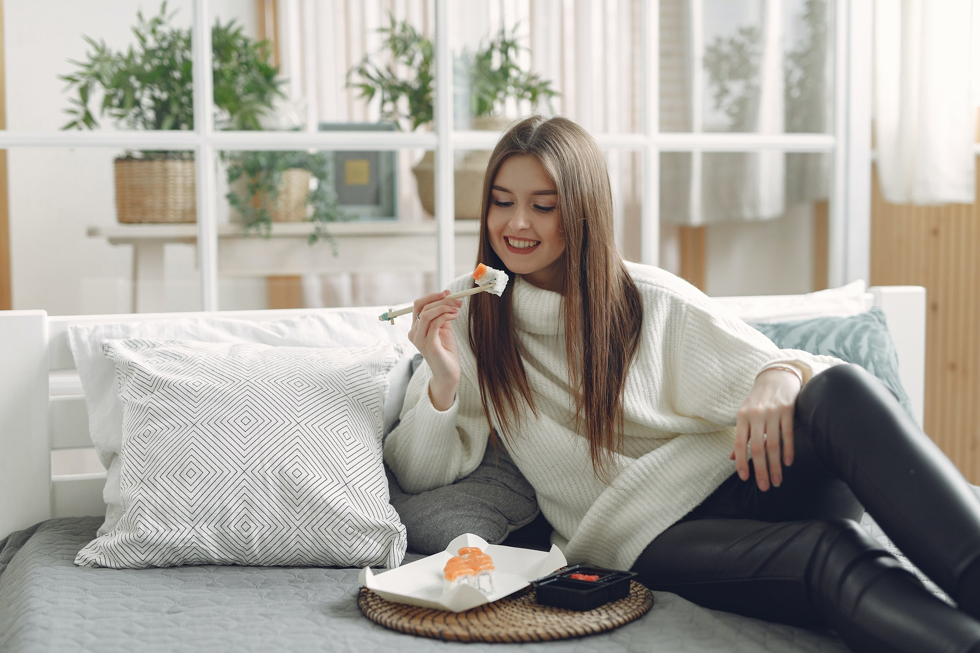 cheerful-young-woman-eating-sushi-at-home-4173302